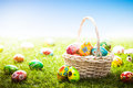 Unique hand painted Easter eggs in basket and lying on grass, blue sky