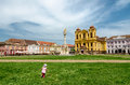 Unirii square in timisoara romania young girl running with roman catholic episcopal church the background of the image Royalty Free Stock Photos