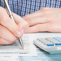 United states of america tax form male filling out tax form to ratio Stock Photography