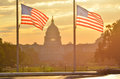 United states capitol building and us flag silhouette at sunrise washington dc two flags Stock Image