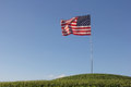 United states flag all alone top of hill on grass blowing in breeze blue sky background Stock Photography