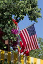 United states flag surrounded by flowers trees and blue sky beautiful saturated colors of the hanging in front of other country s Stock Images