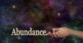 Universal abundance female hand facing up with the word touching the index finger on a deep space night sky background providing Stock Photos