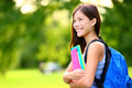 University college student girl looking happy smiling with book or notebook in campus park beautiful young mixed race asian Stock Images