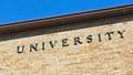 University sign on a brick wall Stock Photography