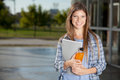 University student candid portrait of a standing with notes and drink Royalty Free Stock Images