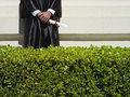 University student in graduation gown holding diploma mid section hedge in foreground Royalty Free Stock Photos