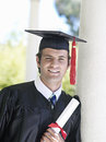 University student in graduation gown and mortar board holding diploma smiling close up portrait Stock Photo