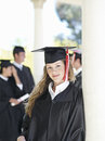 University student in graduation gown and mortar board smiling portrait focus on foreground Stock Images