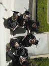 University students in graduation gowns and mortar boards holding diploma portrait overhead view Royalty Free Stock Photo