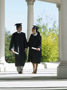 University students in graduation gowns and mortar boards walking in colonnade holding diplomas Royalty Free Stock Image