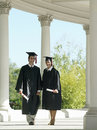 University students in graduation gowns and mortar boards walking in colonnade holding diplomas Royalty Free Stock Photography
