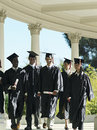 University students in graduation gowns and mortar boards walking in colonnade smiling Stock Image