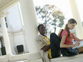 University students studying near colonnade man leaning book against woman s back smiling tilt men Stock Photography