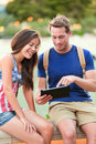 University students on tablet computer happy couple using app outside asian women and young caucasian man Royalty Free Stock Image