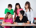 University students using digital tablet at desk teenage in classroom Royalty Free Stock Photography