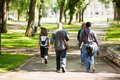 University students walking on campus road rear view of with backpacks Stock Images