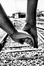 Into the unknown together a dramatic photograph of a couple holding hands while walking along railroad tracks Stock Image
