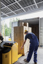 Unloading of articles in the warehouse by a worker Stock Image