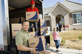 Unloading delivery van in front of house family and worker a new Stock Photos
