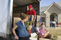 Unloading delivery van by new house family and worker truck of cardboard boxes Stock Photos