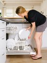 Unloading the dishwasher photo of a blond female leaning over and her Stock Images