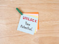 Unlock your potential handwriting on colorful notepaper and blackboard with wood background business concept Royalty Free Stock Photo