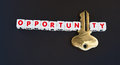 Unlocking an opportunity text inscribed in uppercase red letters on small white cubes with letter i replaced by golden key dark Stock Photography