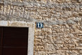 Unlucky thirteen house number sign on old stone wall Royalty Free Stock Images