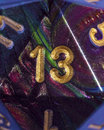 Unlucky thirteen number is rolled on a glittery twenty sided die Stock Image