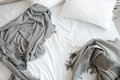 Unmade bed with pillow and gray blankets top view Royalty Free Stock Photo