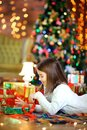 Unny girl lies on the floor and opens gifts