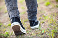 Unrecognizable man in rubber shoes stepping on footpath, rear view, closeup Royalty Free Stock Photo