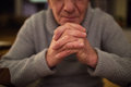 Unrecognizable senior man at home praying, hands clasped togethe Royalty Free Stock Photo