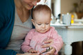 Unrecognizable young mother holding her little daughter, feeding Royalty Free Stock Photo
