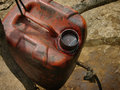 Unrefined crude oil is collected in a jerry can at a heavily polluted illegal oil field kadewan east java indonesia Royalty Free Stock Image