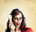 Unreliable female zombie administration clerk handing over a telephone receiver late with a dead phone line Royalty Free Stock Photography