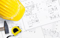 Unrolled construction project on table helmet hammer and measuring tape with free space for text Royalty Free Stock Photo