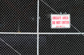 Unsafe area behind a fence with do not enter sign on chain link trespassing black background outdoors Stock Images