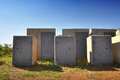 Unsafe safes a grouping of abandoned heavy duty with grass growing all round the base concrete and steel construction an Stock Photo