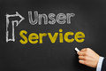 Unser service in german with arrow on blackboard hand writes our Stock Photo