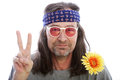 Unshaven male hippie with long shoulder length hair wearing a headband yellow flower and rose coloured glasses making a peace sign Royalty Free Stock Photography
