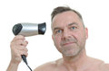 Unshaven man blow drying his short hair middle aged with a handheld hairdryer looking at the camera with a smile head and Royalty Free Stock Photos