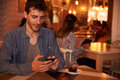 Unshaven millennial with cellphone in restaurant Royalty Free Stock Photo