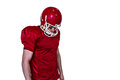Unsmiling american football player looking down on a white background Royalty Free Stock Photo