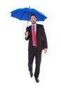 Unsmiling businessman holding an umbrella on white background Stock Image