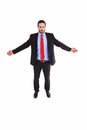 Unsmiling businessman standing with arms outstretched on white background Royalty Free Stock Photo