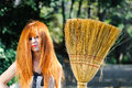 Untidy red haired cute young girl holding broom with Royalty Free Stock Photos