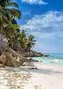 Untouched tropical beach seychelles islands vertical view on an with palm trees and rocks turquoise ocean clear blue sky Stock Photo