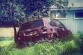 Unused decaying car hatchback parked in grassy area of garden surrounding a wooden building Royalty Free Stock Image